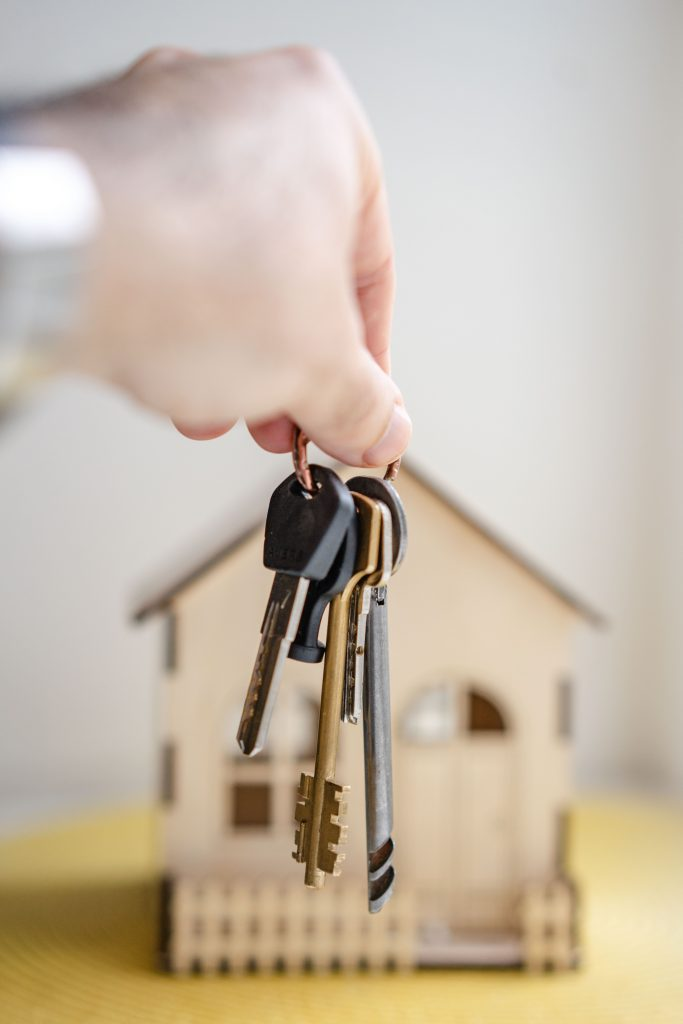 Person waiving keys in front of a model home.